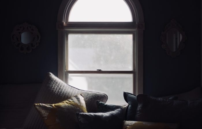a bench covered in pillows in a dimly lit room with light piercing through a large window