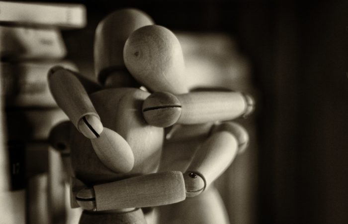 Two wooden dolls embracing each other