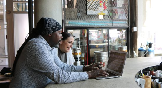 man and woman looking at a laptop in a cafe