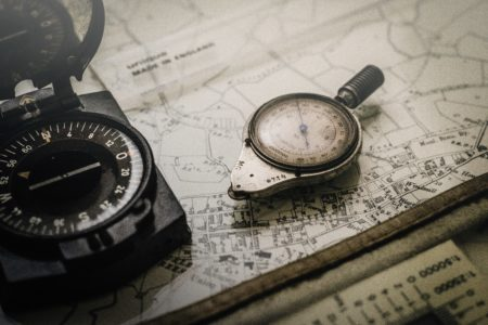 grayscale compass on top of a map