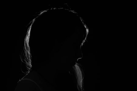 The silhouette of a woman shrouded in darkness
