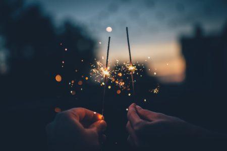 two people holding firecracker sticks