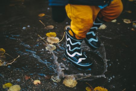 a toddler jumping in a puddle of rain