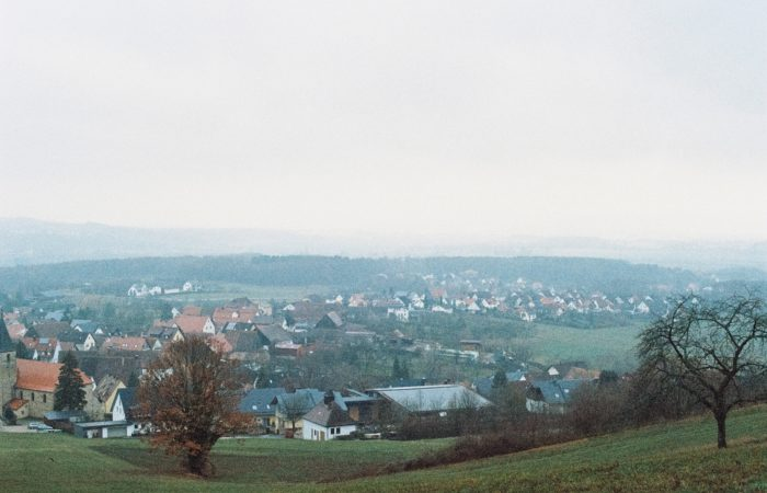 A foggy village seen from atop a hill