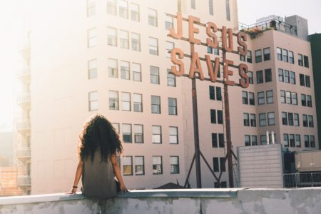 Woman sitting on roof looking up at a sign that reads Jesus Saves