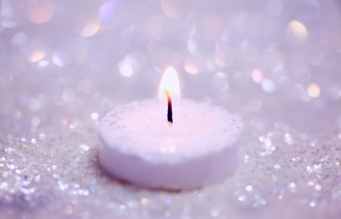 White votive candle on snow