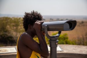 a lady looking through a telescope