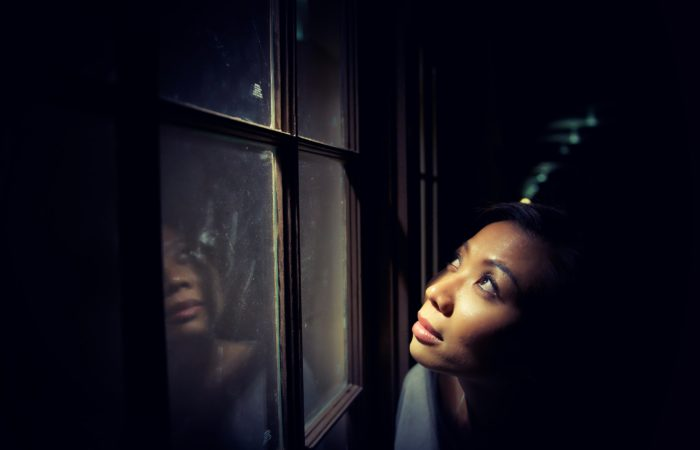 A woman in a dark room gazing into a light outside her window
