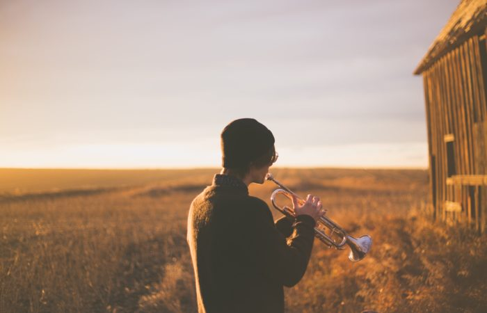 A man playing a trumpet in a field
