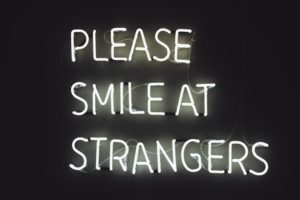 "A black and white sign that reads ""please smile at strangers"""