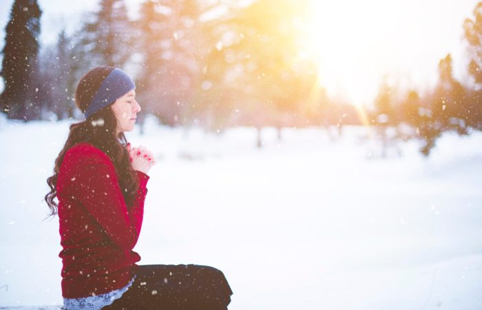 a woman praying in the snow