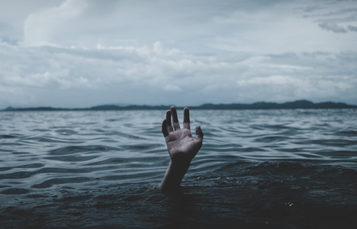 A hand reaching up from out of choppy water