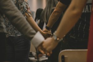 people holding hands in church