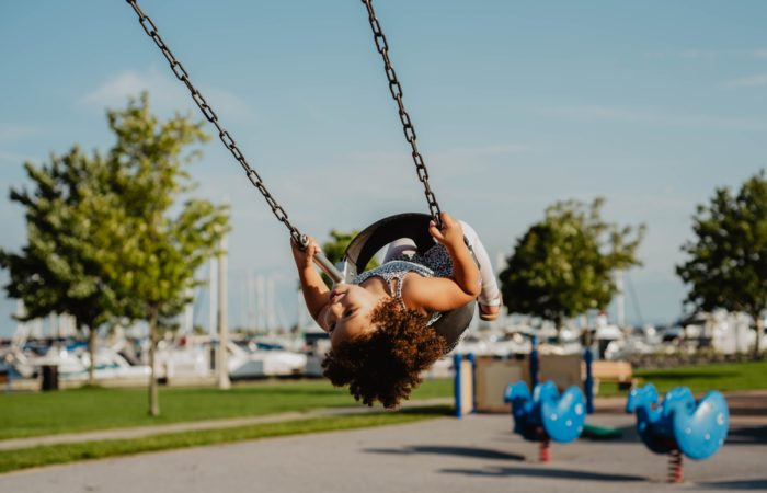 child on tire swing at park