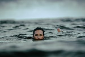 a woman calmly swimming through deep dark water