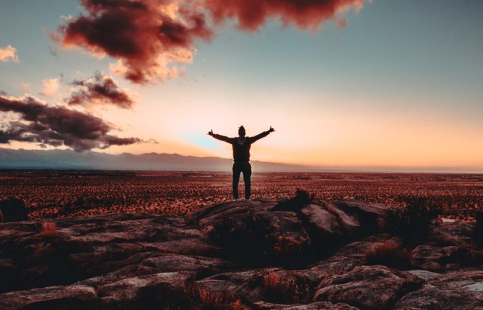 person standing in praise watching the sky