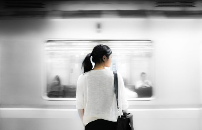 a woman watching the subway train race past her