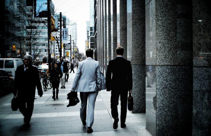 the backs of businessmen walking down the street