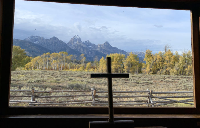 A cross in front of a window with the Grand Tetons seen through the window