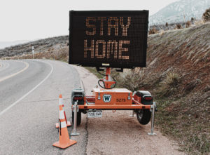 highway road sign that says stay home