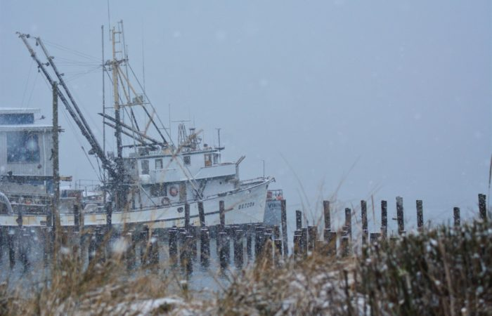 A fishing boat on a rainy, snowy day