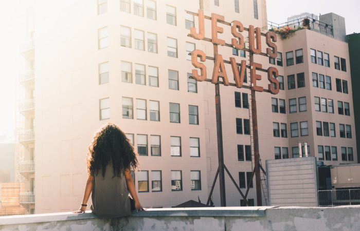 "A woman sitting on a roof looking at a sign that says ""Jesus Saves"""