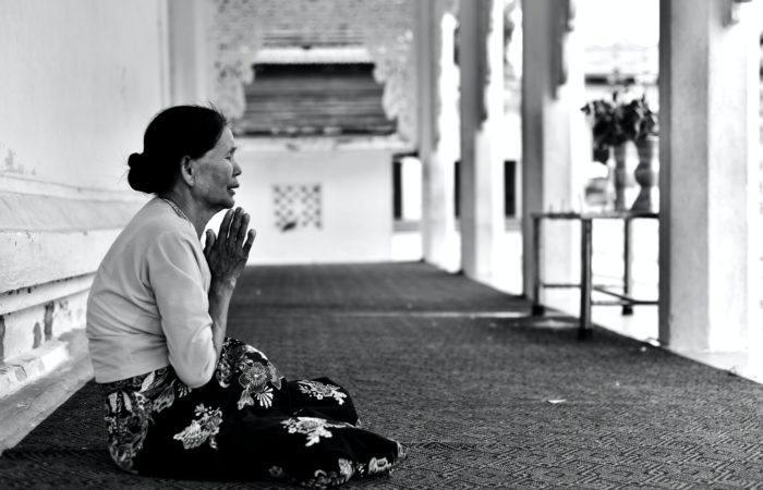 A woman seated on the floor praying