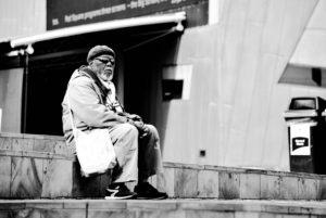 An elderly man sitting on stairs