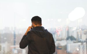 A man on his cellphone with a skyline in the background
