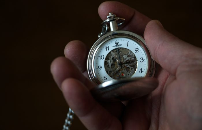 A hand holding a pocket watch