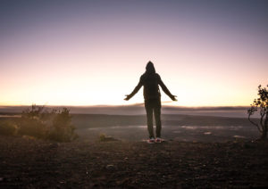 A person standing on a hill at sunrise in a prayerful posture