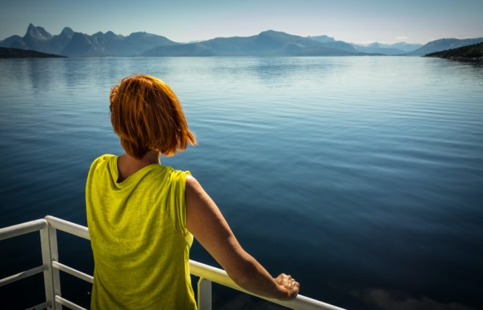 A woman looking out over a lake and mountains