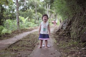 A crying toddler on a forest path