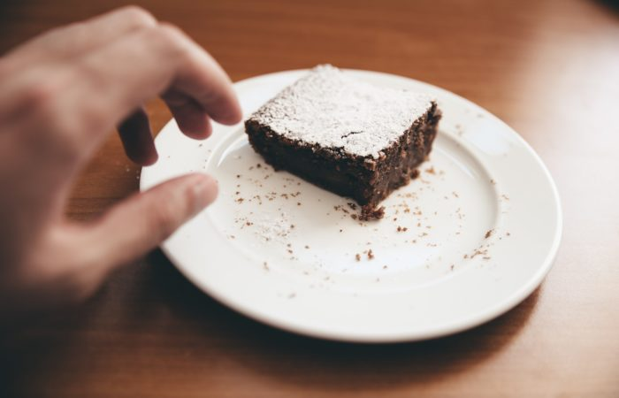 A hand reaching for a brownie on a plate