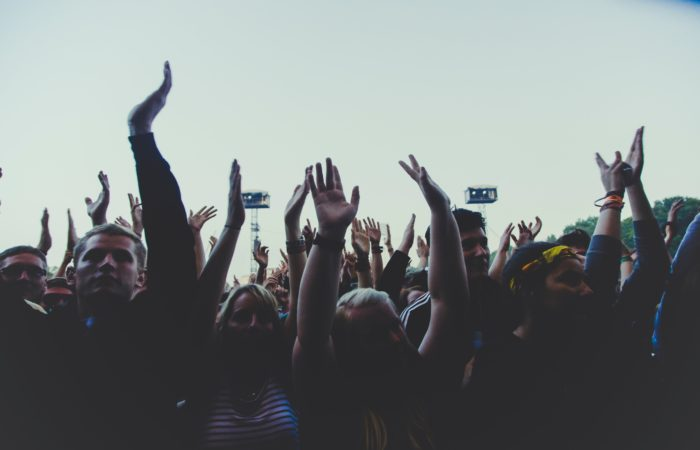 A crowd of people with their hands in the air