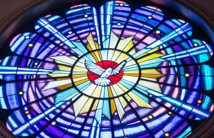 A stained glass window with a dove representing the Holy Spirit in the middle
