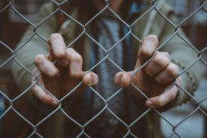 Hands gripping a barbed wire fence