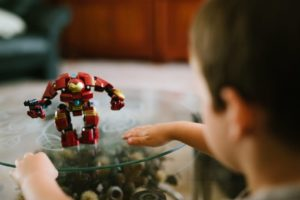 A young boy looking at an Iron Man toy on a table