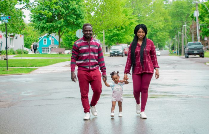 A young couple walking down the street with a toddler in between them