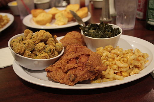 A plate full of fried chicken, macaroni, okra, and greens