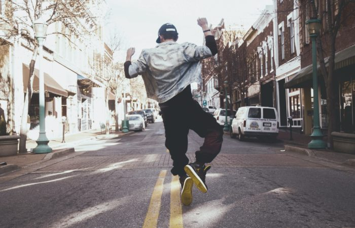 A man jumping into the air and clicking his heels on a city street