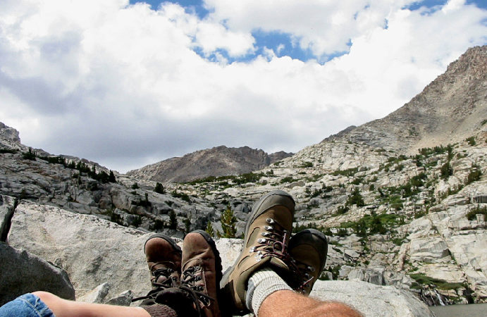 The boots of two people sitting and looking out over the Sierra