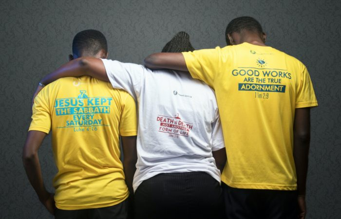 Three people with their backs to the camera and their arms around each others' shoulders, wearing tshirts with religious slogans, including a reference to the sabbath and Luke 4:16