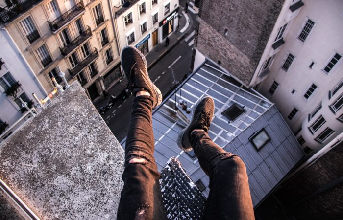 The legs of someone sitting on top of a skyscraper