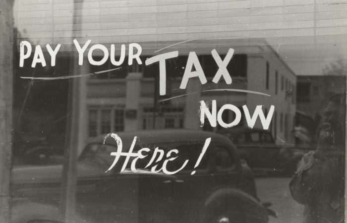 "A 1930's-era store window with a sign reading ""Pay Your Tax Now"""