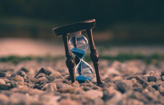 An hourglass on a sandy beach