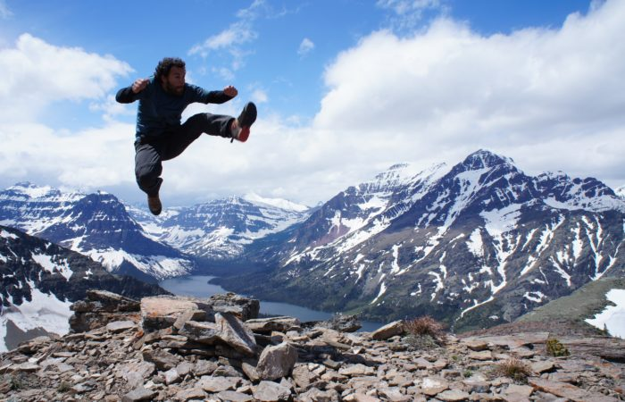 A man leaping with mountain scenery behind him