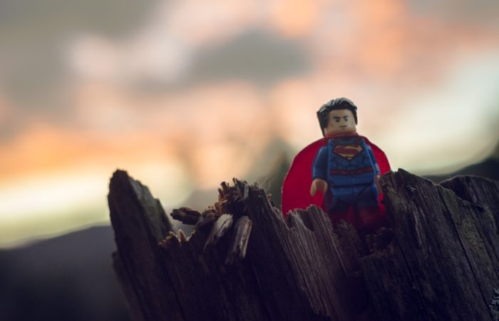 A Lego figure of Superman standing on a miniature cliff