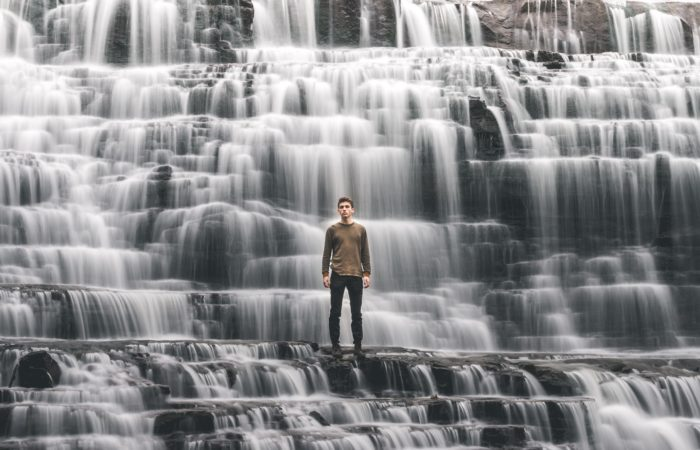A man standing on rocks with water cascading down around him