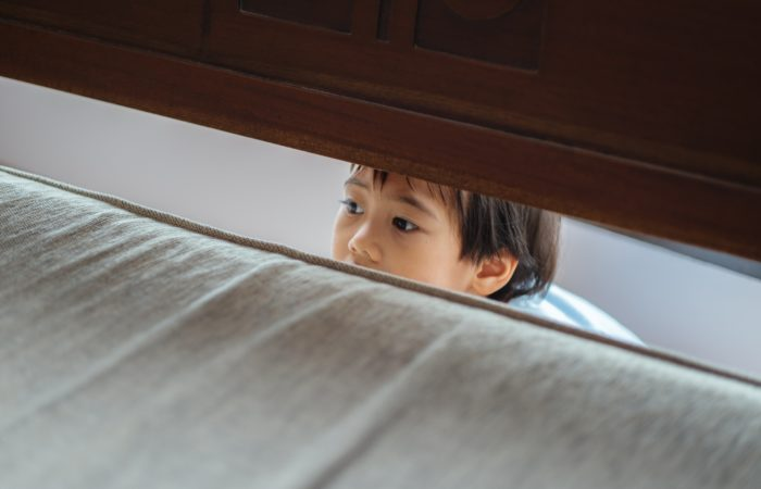 A child hiding behind a bed
